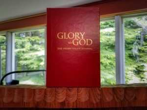 The Presbyterian Hymnal book atop a podium with -Glory to God- in gold letters